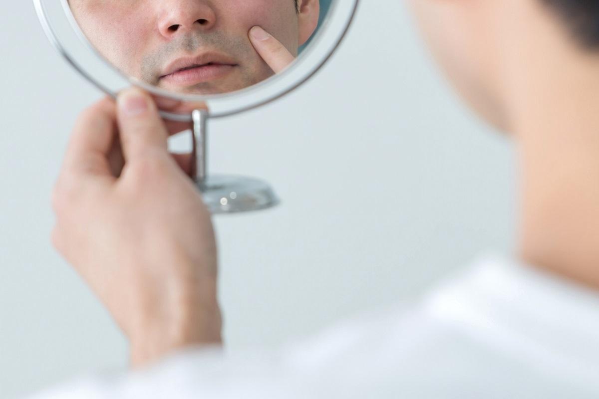 鏡を見て髭を気にしている男性