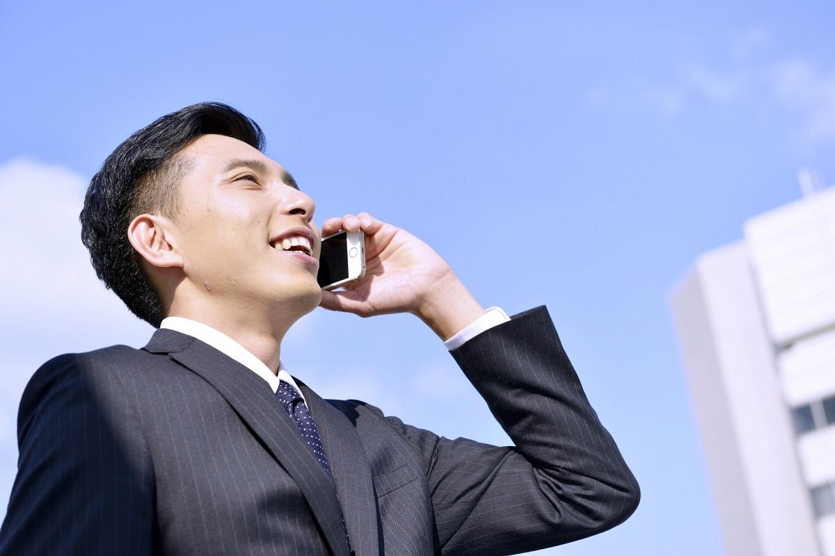 青空の下で笑顔で電話をしているサラリーマンの男性