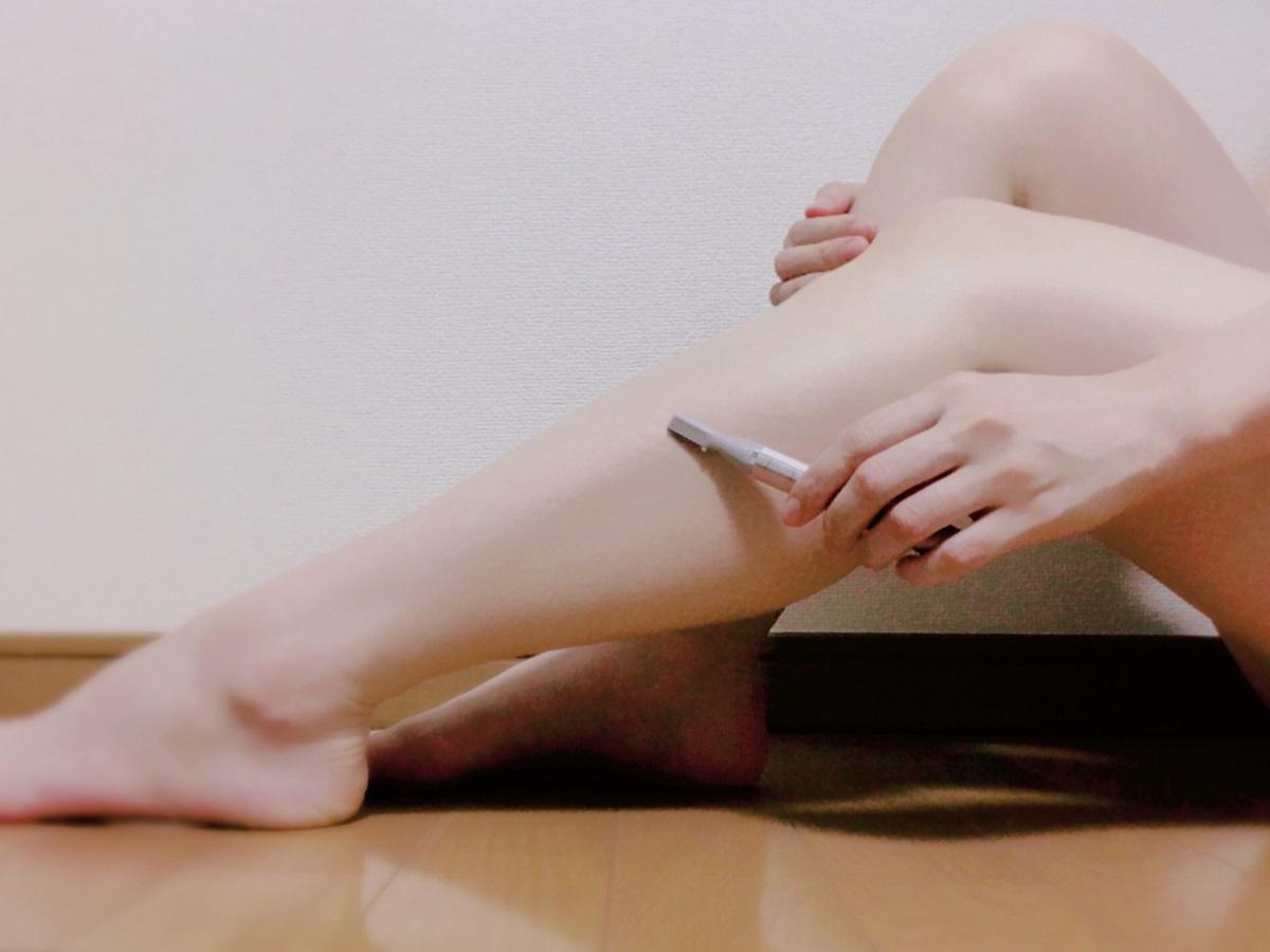 部屋で電気シェーバーで脚の毛の自己処理をしている女性