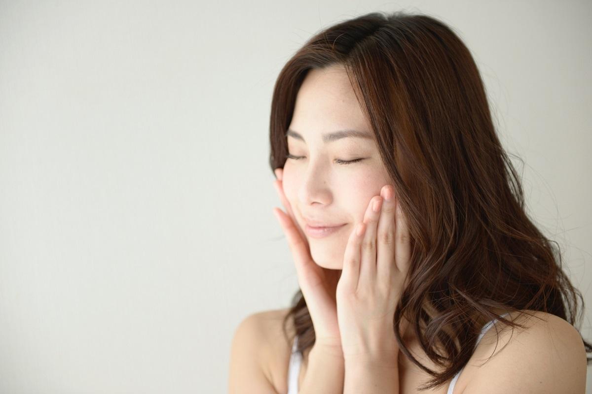 医療レーザー脱毛をして美肌になった顔に触れて満足げな女性