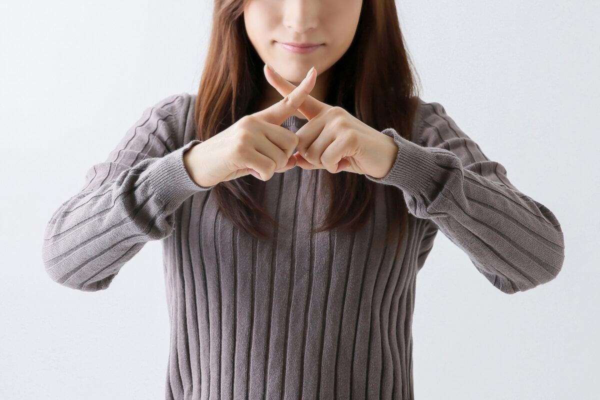 NGマークを指で作っている女性
