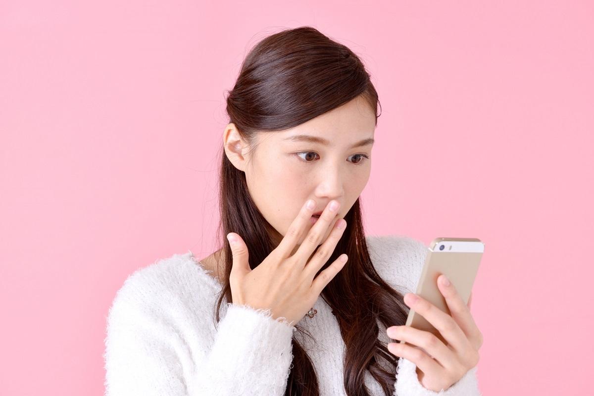 スマートフォンを見てびっくりしている女性
