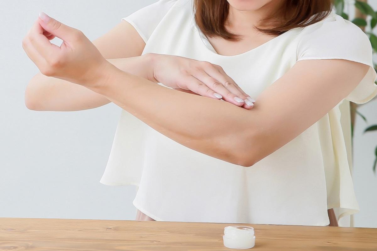 クリームで腕を保湿している女性
